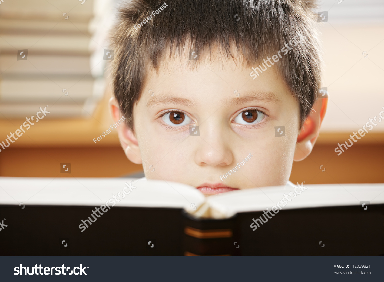 Black Boy Book Cover : Boy looking over open book with black cover closeup photo