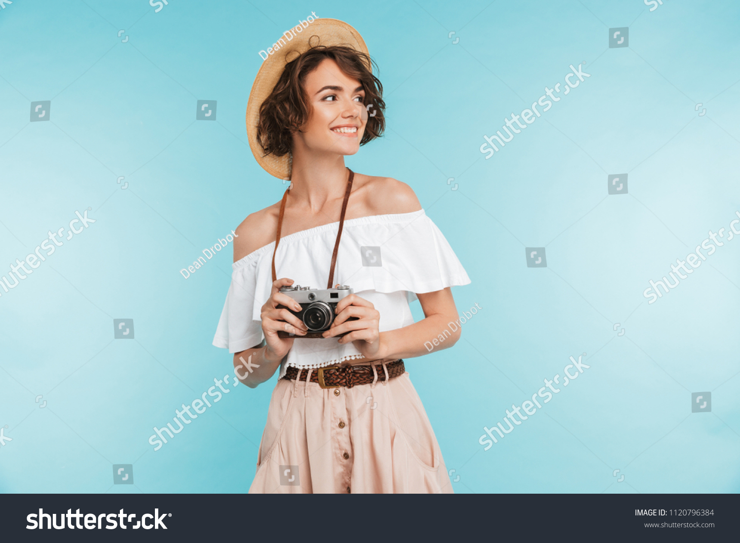 Portrait of a smiling young woman in summer hat standing with photo camera and looking away at copy space isolated over blue background