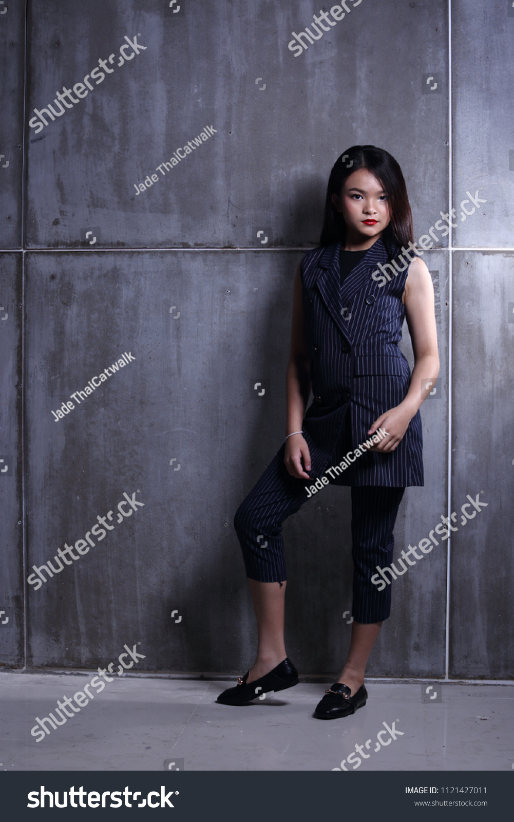 Business Kid Girl in formal suit stand on dark abstract background, studio lighting copy space for text logo, black hair eleven years old full length snap body, Fashion Face Eyes Heart Summer #1121427011