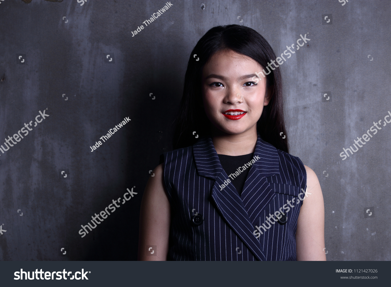 Business Kid Girl in formal suit stand on dark abstract background, studio lighting copy space for text logo, black hair eleven years old portrait half body, Fashion Face Eyes Heart Summer #1121427026