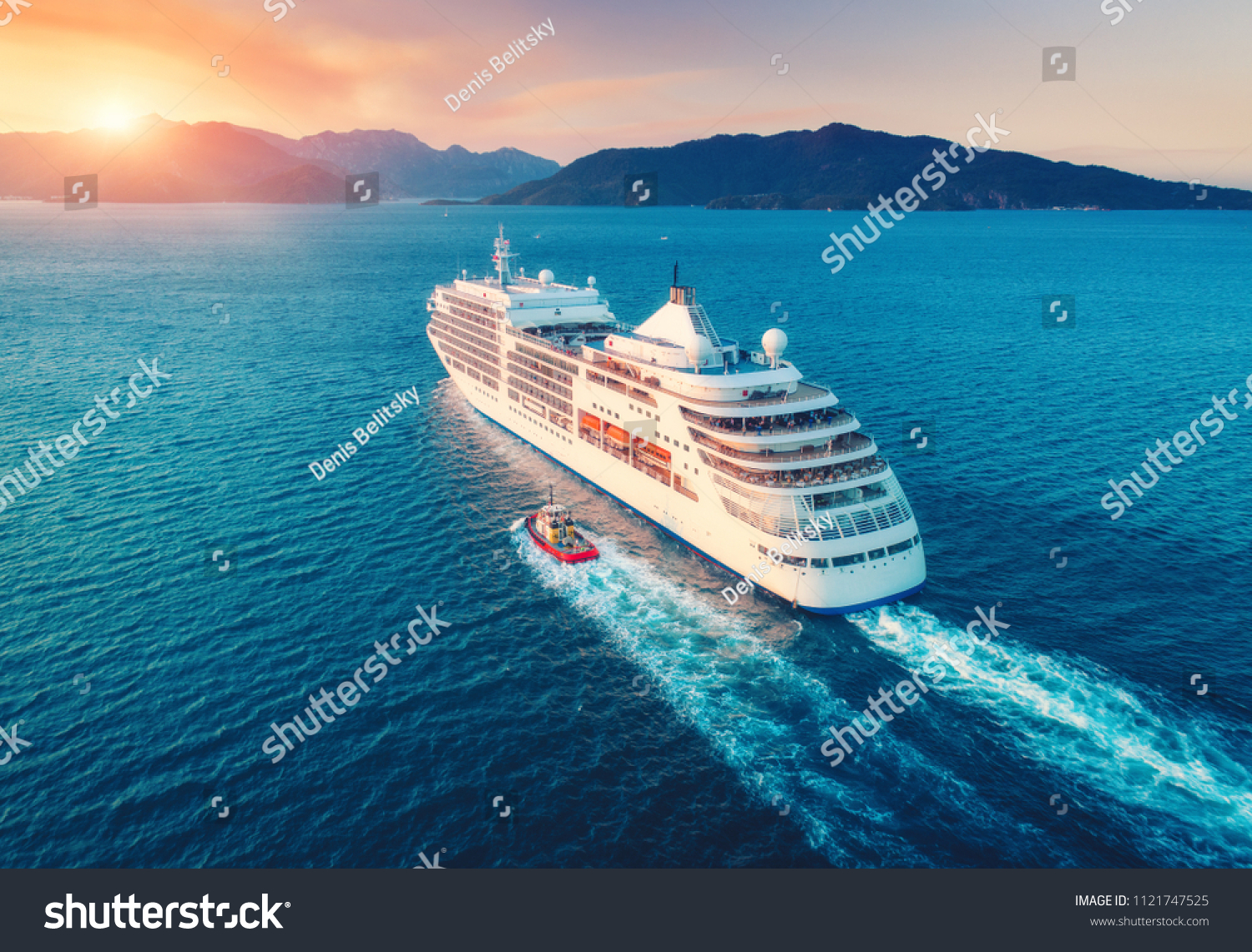 Cruise ship at harbor. Aerial view of beautiful large white ship at sunset. Colorful landscape with boats in marina bay, sea, colorful sky. Top view from drone of yacht. Luxury cruise. Floating liner #1121747525