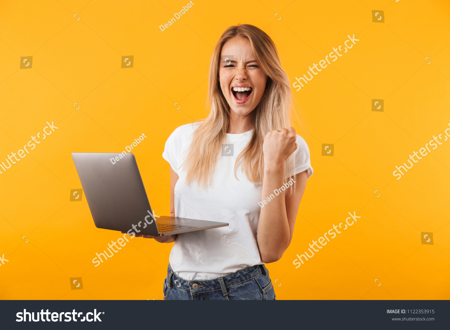 Portrait of an excited young blonde girl holding laptop computer and celebrating success isolated over yellow background #1122353915