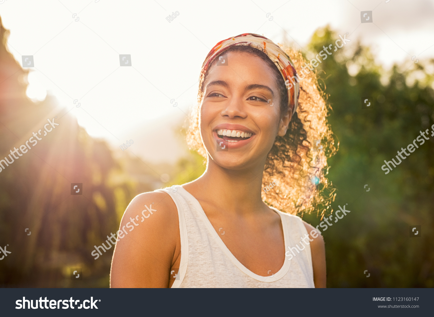Portrait of beautiful african american woman smiling and looking away at park during sunset. Outdoor portrait of a smiling black girl. Happy cheerful girl laughing at park with colored hair band. #1123160147