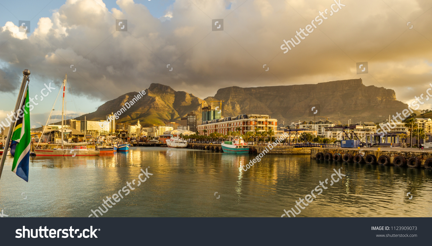 Cape Town harbor, Victoria and Alfred Waterfront at sunset with south african flag. Table mountain in background, South Africa beautiful destination