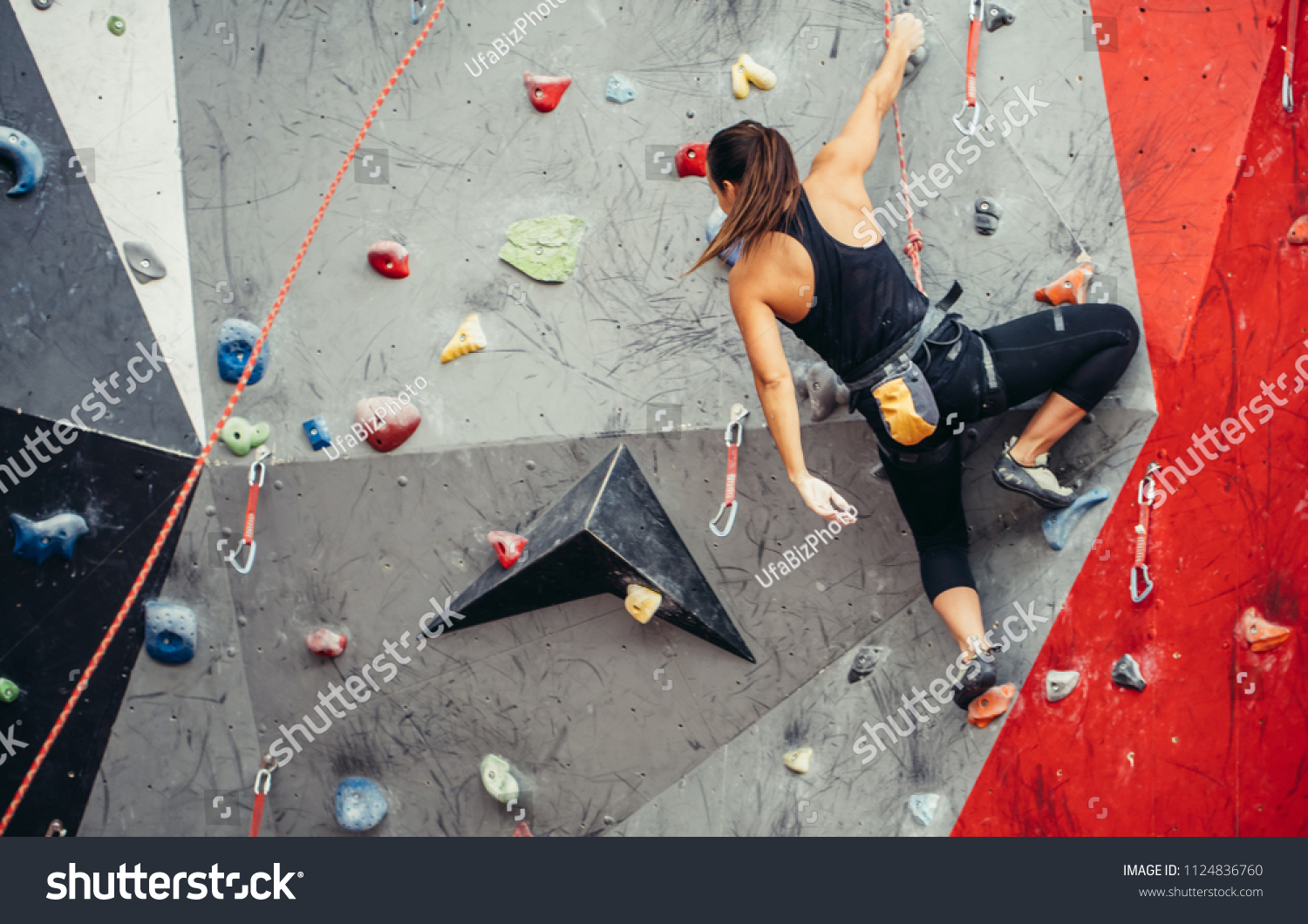 Sporty successful business woman being busy at her hobby-bouldering. Well equipped woman training in a colorful climbing gym, preparing to summer mountain ascend #1124836760