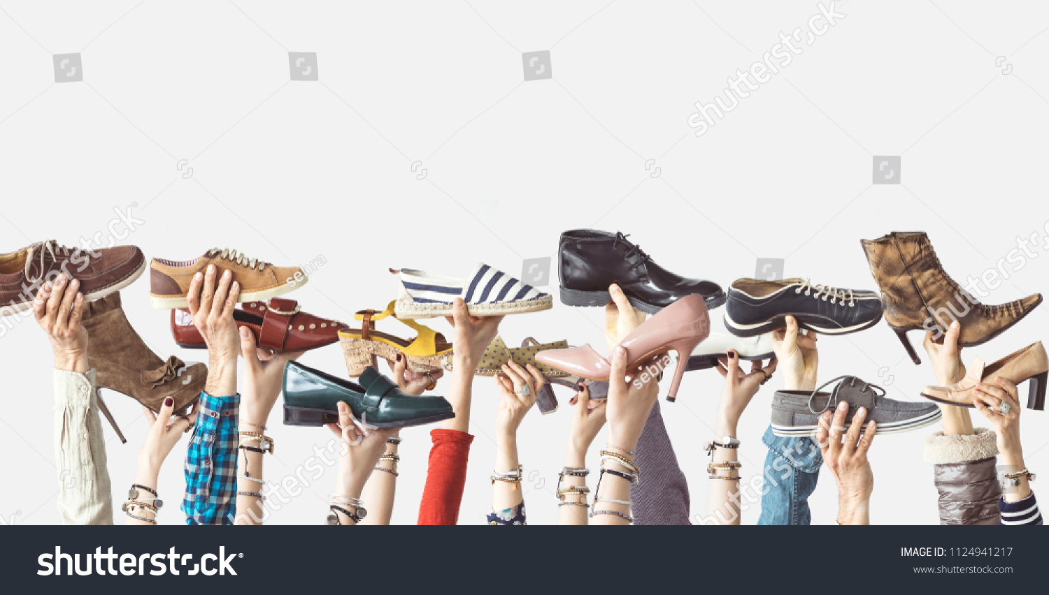 Hands holding different shoes on isolated background #1124941217