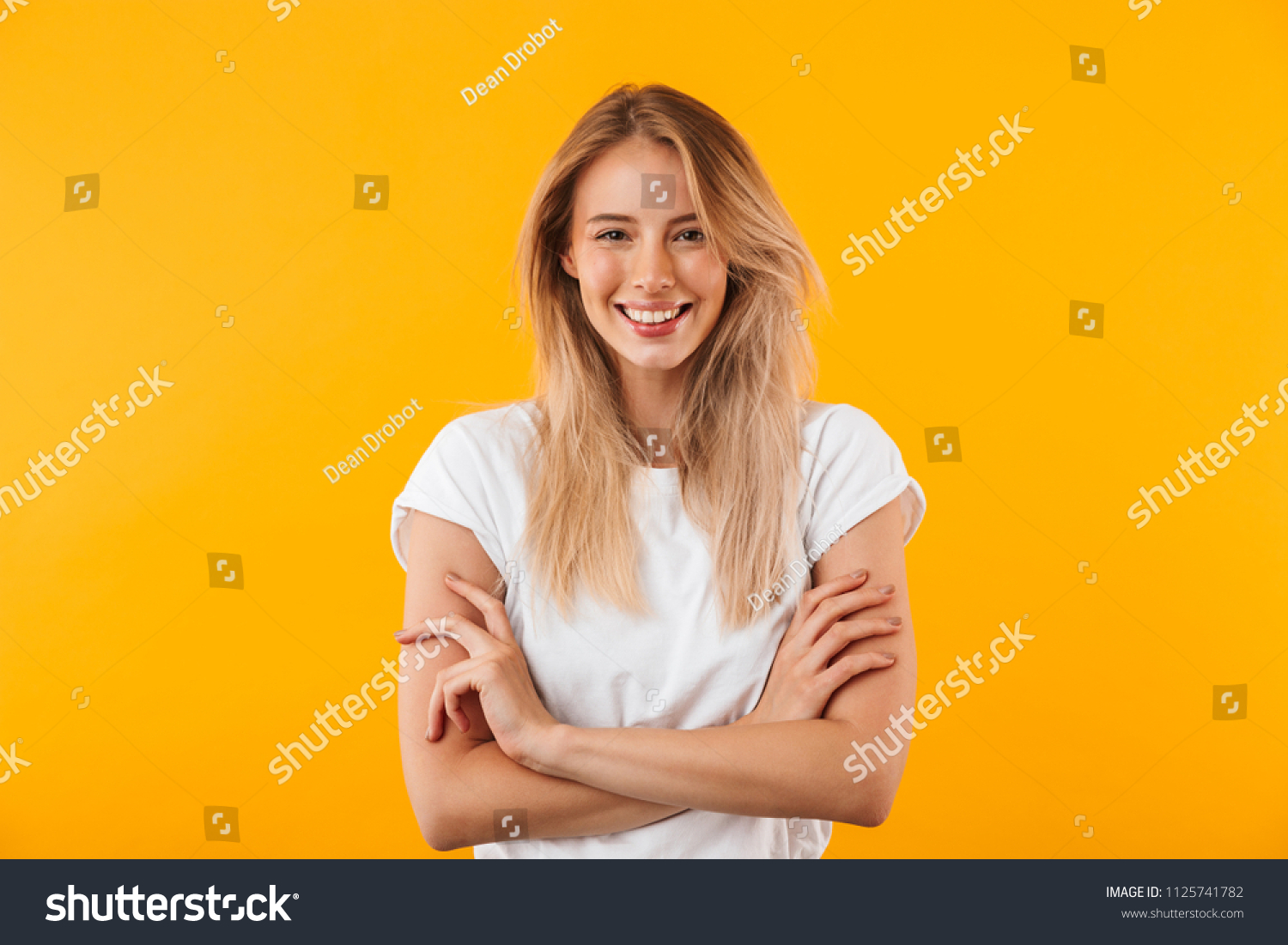 Portrait of a smiling blonde young woman standing with arms folded isolated over yellow background #1125741782