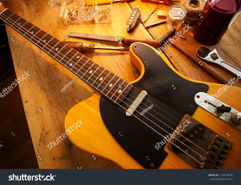 guitar on guitar repair desk vintage electric guitar on a guitar repair work shop single. Black Bedroom Furniture Sets. Home Design Ideas