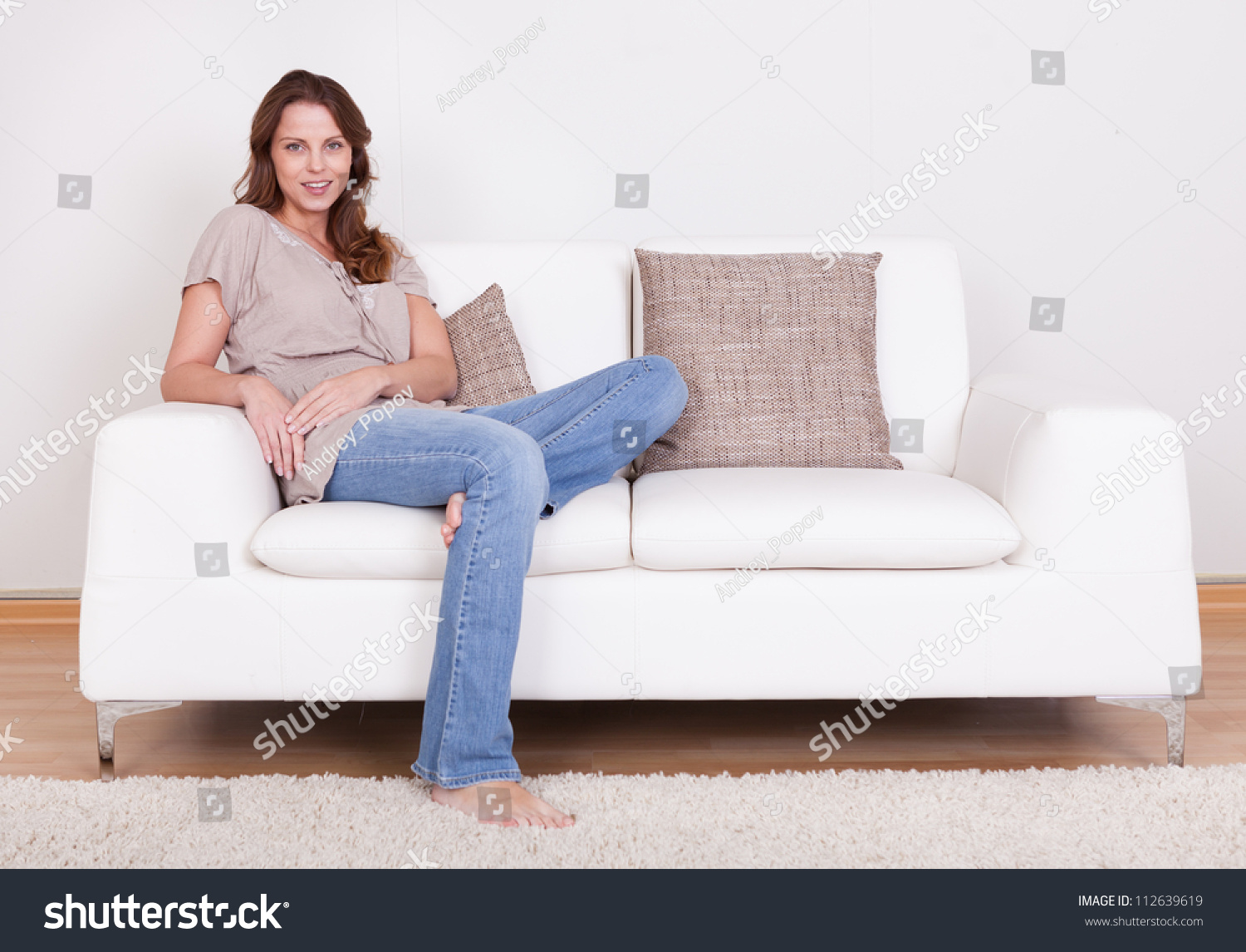 Casual Barefoot Woman In Jeans Sitting On A Couch In Her