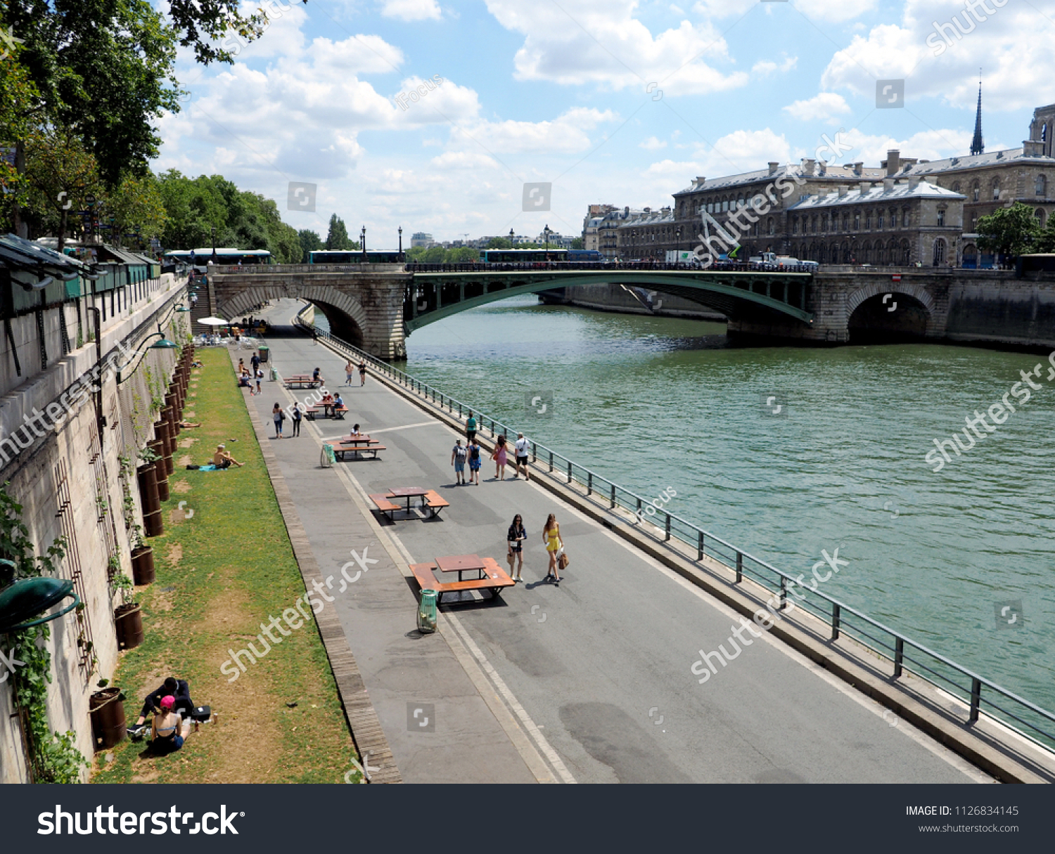 PARIS, FRANCE - JULY 3, 2018: People enjoy taking a stroll along river Seine on July 3, 2018 in Paris, France.