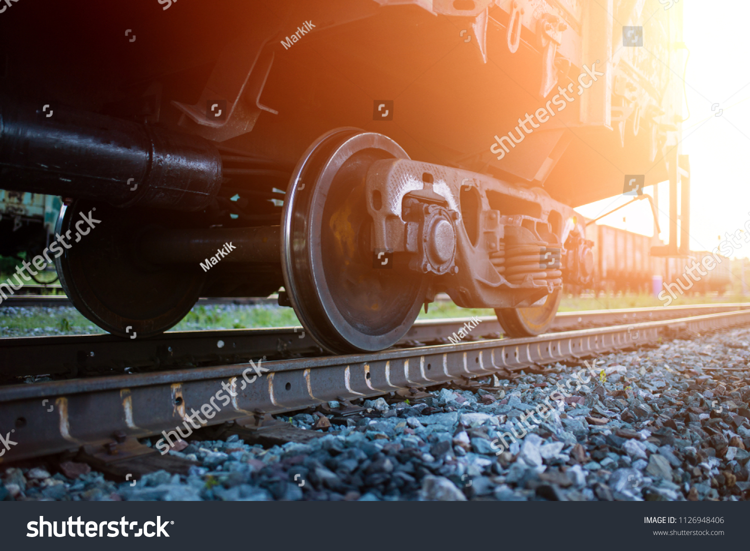 The railway engine of a freight locomotive that crosses the desert during sunset. Large transport of goods in tanks by rail. railway rails #1126948406