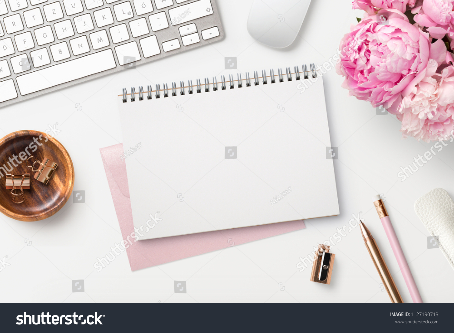 feminine workspace / desk with blank open notepad, keyboard, stylish office / writing supplies and pink peonies on a white background, top view #1127190713