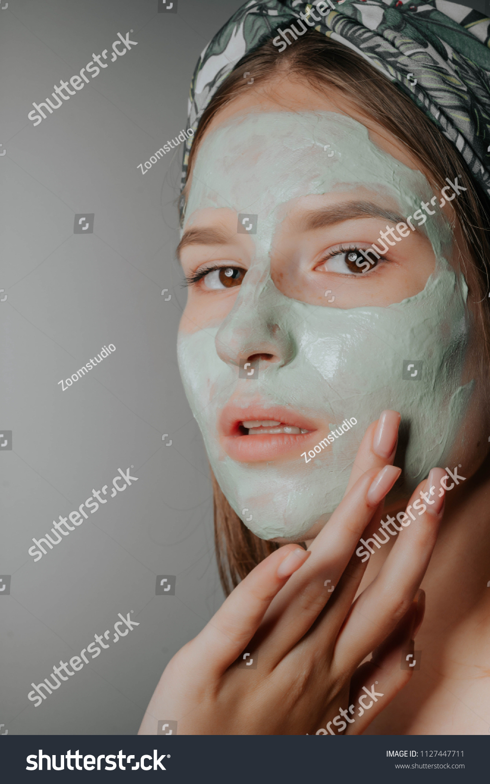 Spa teen girl applying facial clay mask. Beauty treatments. She holds a  cucumber.