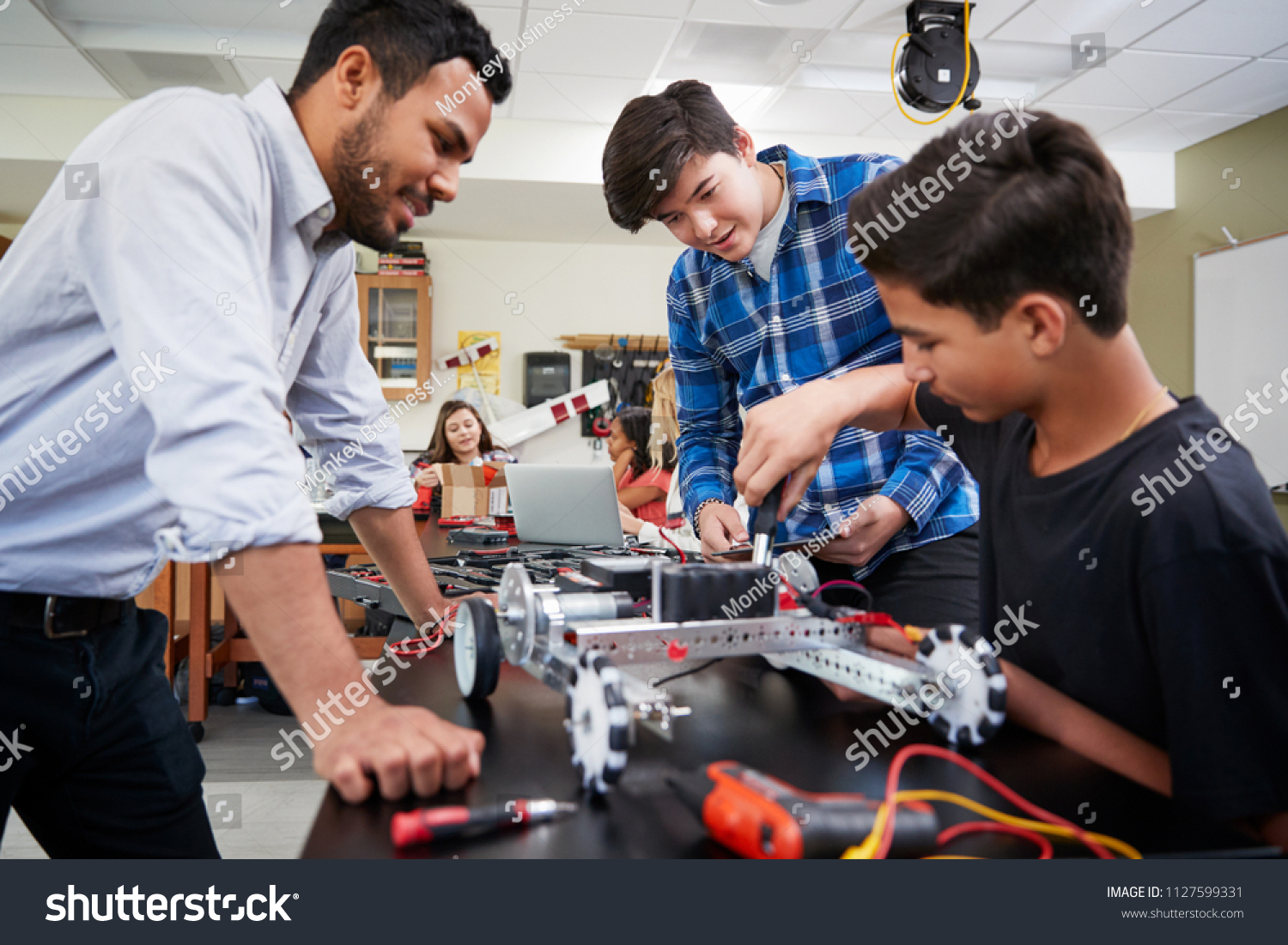 Teacher With Male Pupils Building Robotic Vehicle In Science Lesson #1127599331