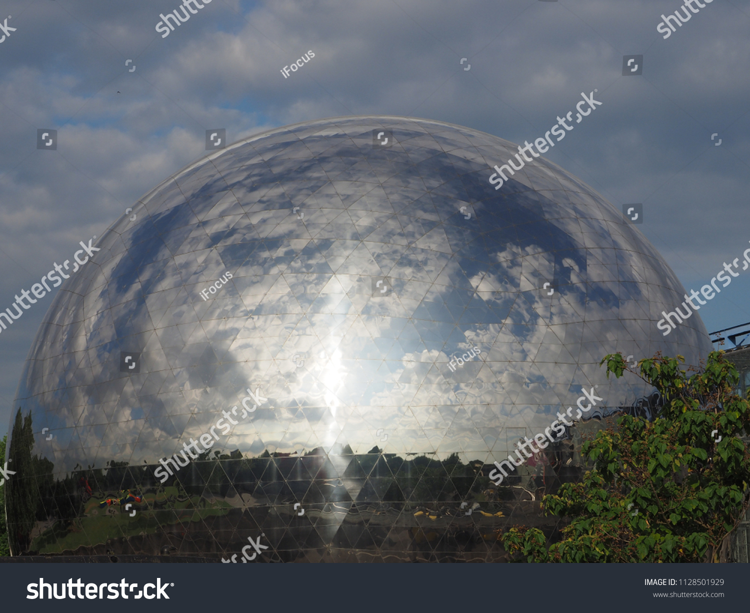 PARIS, FRANCE - JULY 4, 2018: The landscape reflects in geodesic dome La Géode at City of Science and Industry on July 4, 2018, in Paris, France