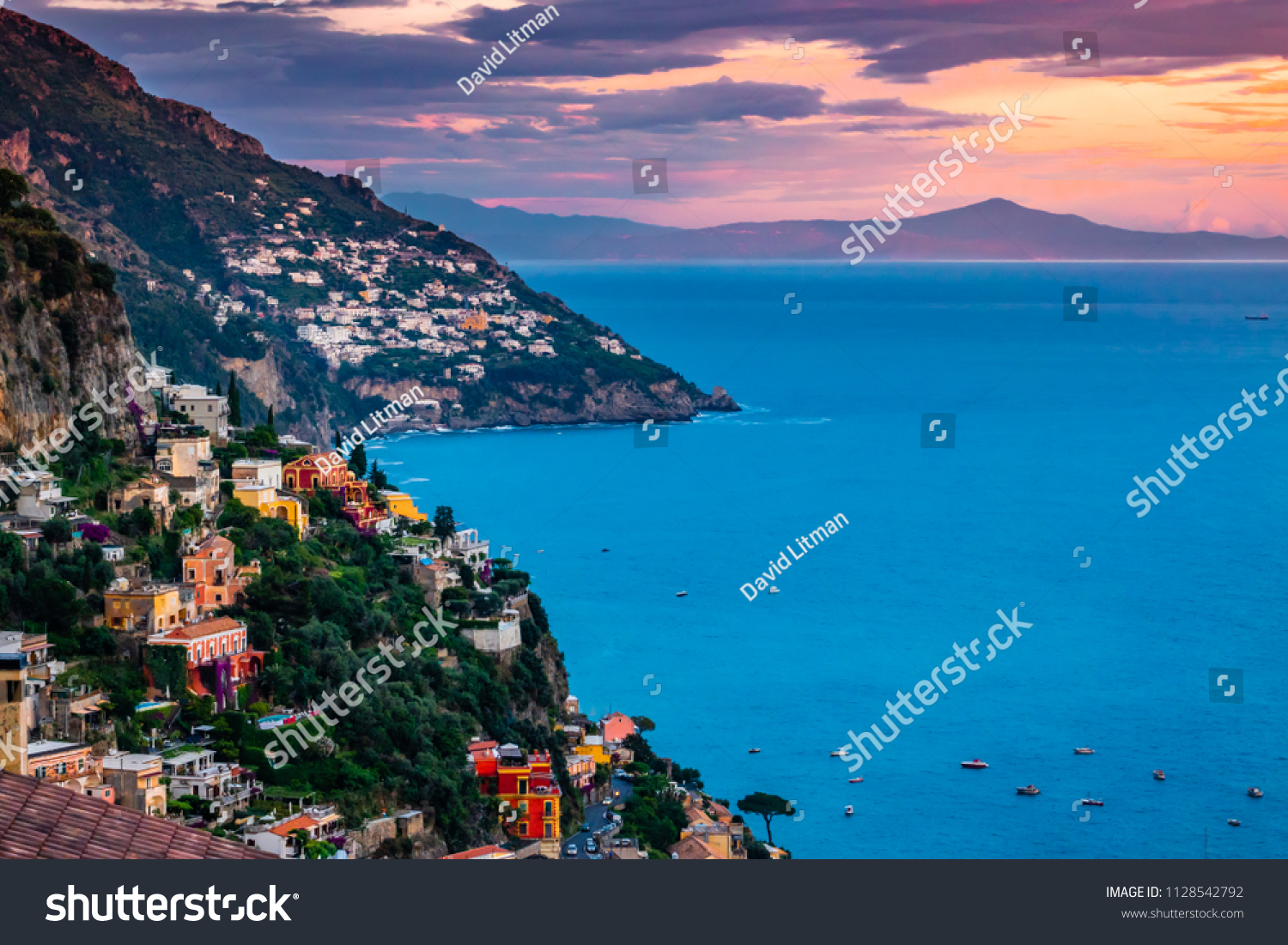 Panoramic sunset view of the Amalfi Coast of southern Italy, including colorful buildings of Positano in the foreground as well as Praiano in distance.