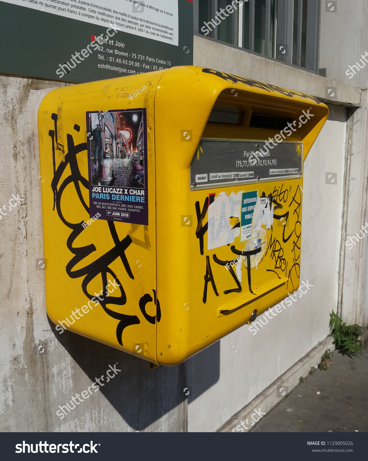 PARIS, FRANCE - JULY 6, 2018: A yellow mailbox at a post office is vandalized on July 6, 2018 in Paris, France.