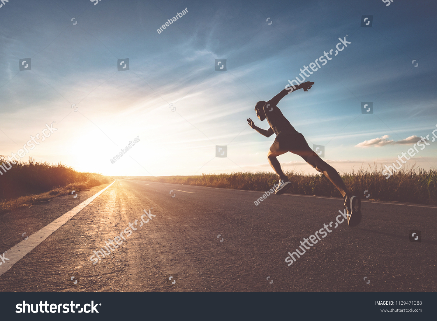 The man with runner on the street be running for exercise. #1129471388