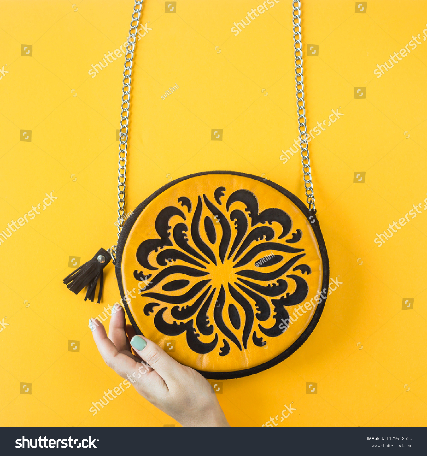 Bright orange round bag with a black pattern with a chain on a yellow  background with woman s hand. Autumn accessories concept. Top view ba262a4ff9dd7