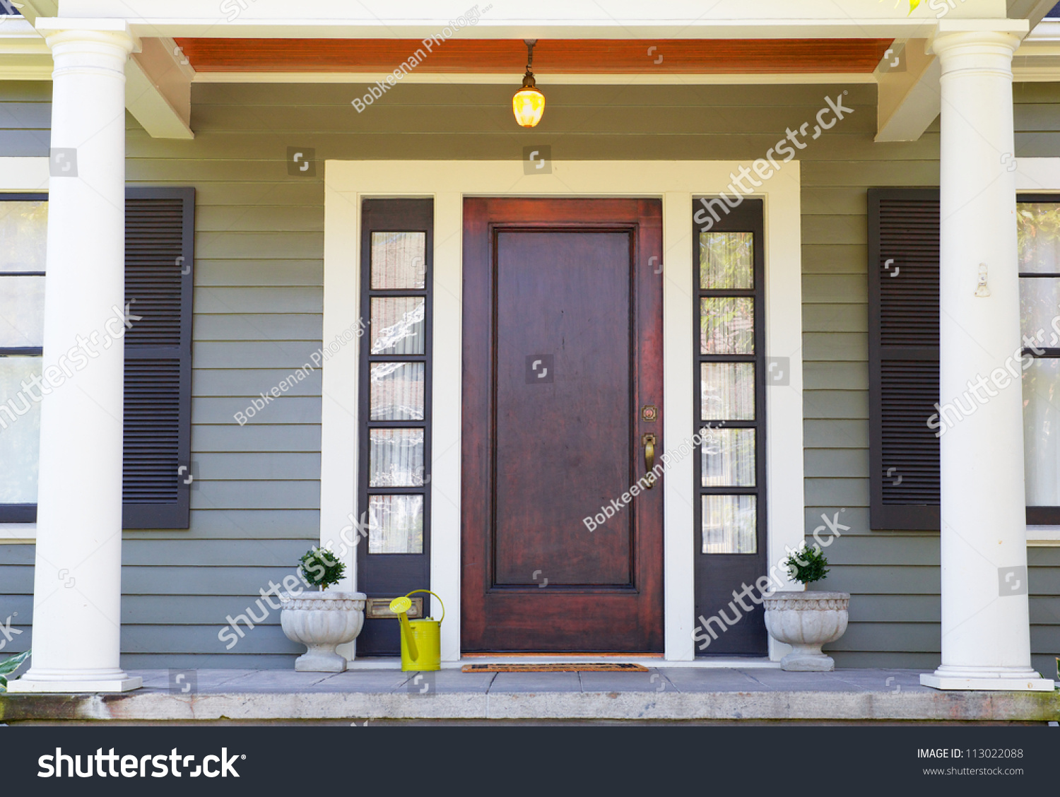 Brown stained front door on home stock photo 113022088 shutterstock brown stained front door on a home with bordering window and a pillared porch rubansaba