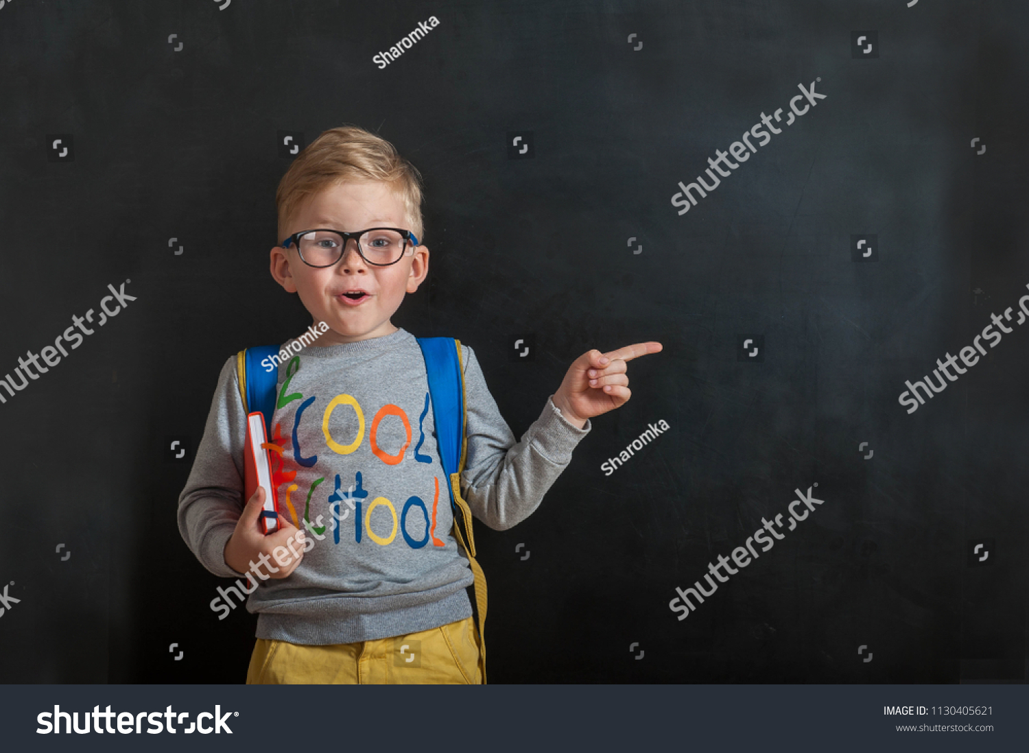 Back to school. Funny little boy in glasses pointing up on blackboard. Child from elementary school with book and bag. Education. Kid with a book #1130405621