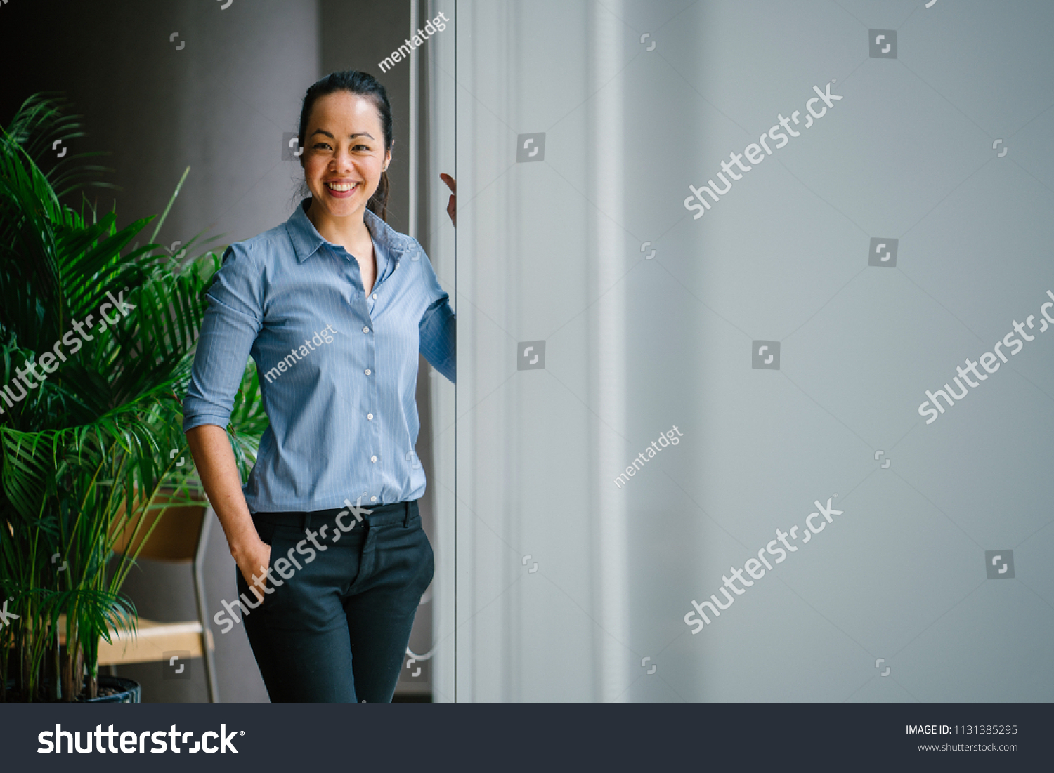 Portrait of a young, attractive and confident Chinese Asian business woman in a meeting room during the day. She is standing by the glass windows and smiling as she leans on the window ledge.  #1131385295
