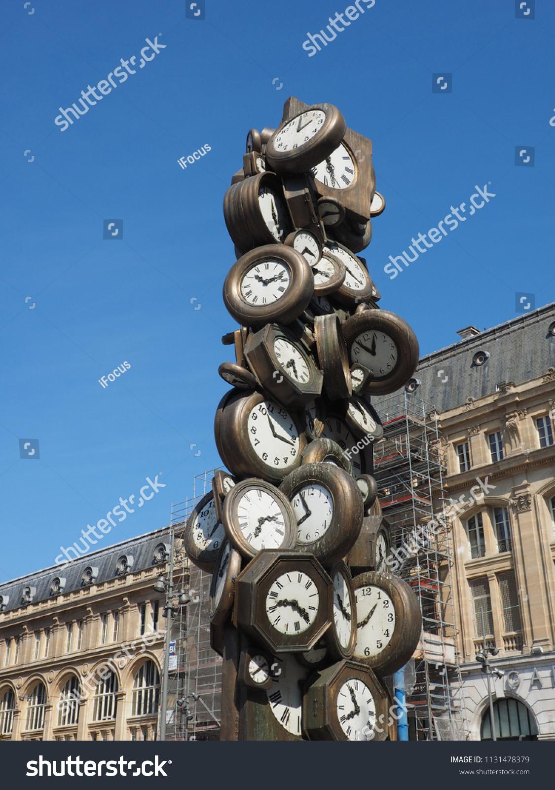 "PARIS, FRANCE - JULY 10. 2018: Arman Fernandez' sculpture ""L'heure de tous"" soars into blue sky in front of St-Lazare railway station on July 10, 2018 in Paris, France."
