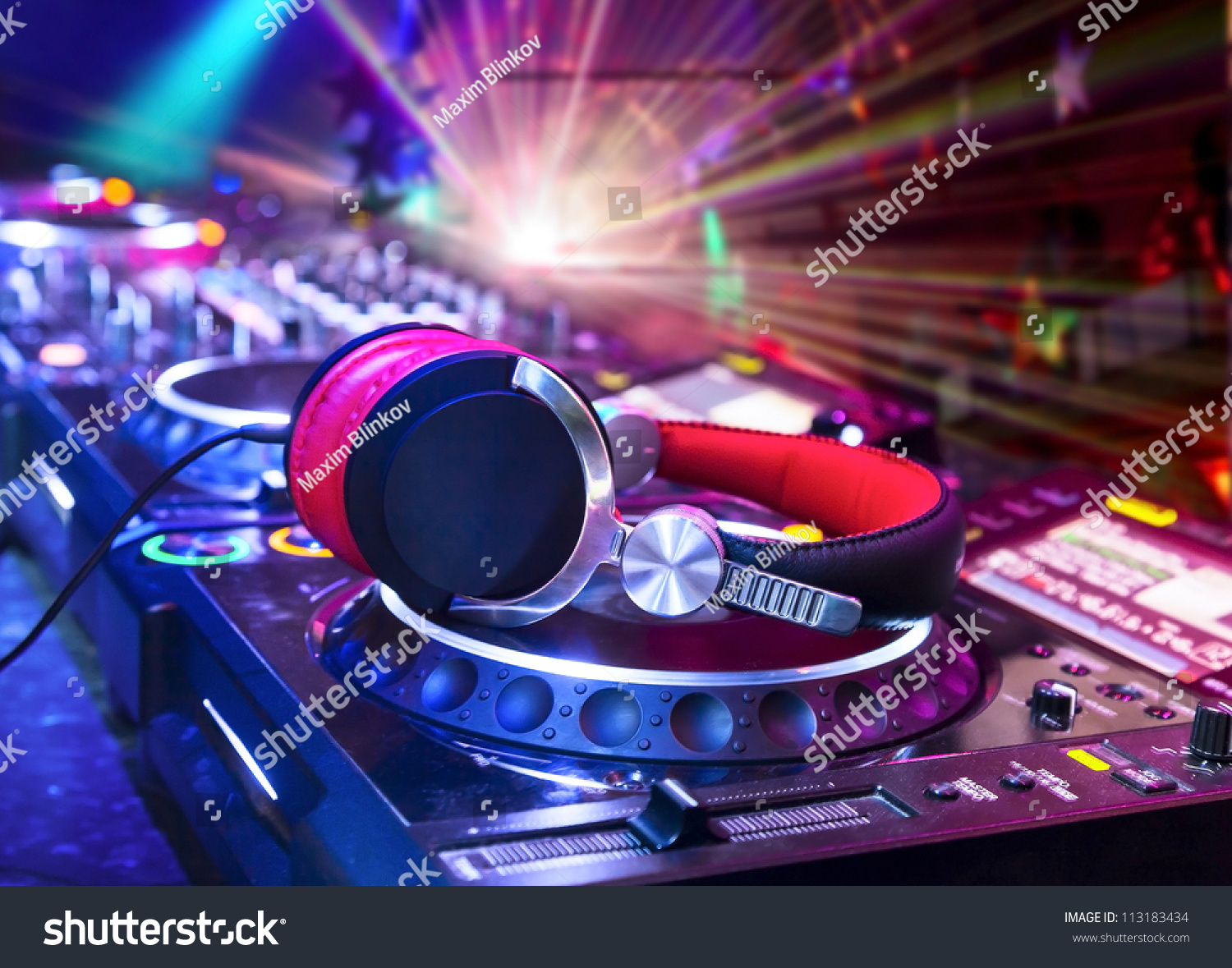 Dj mixer with headphones at nightclub.  In the background laser light show #113183434