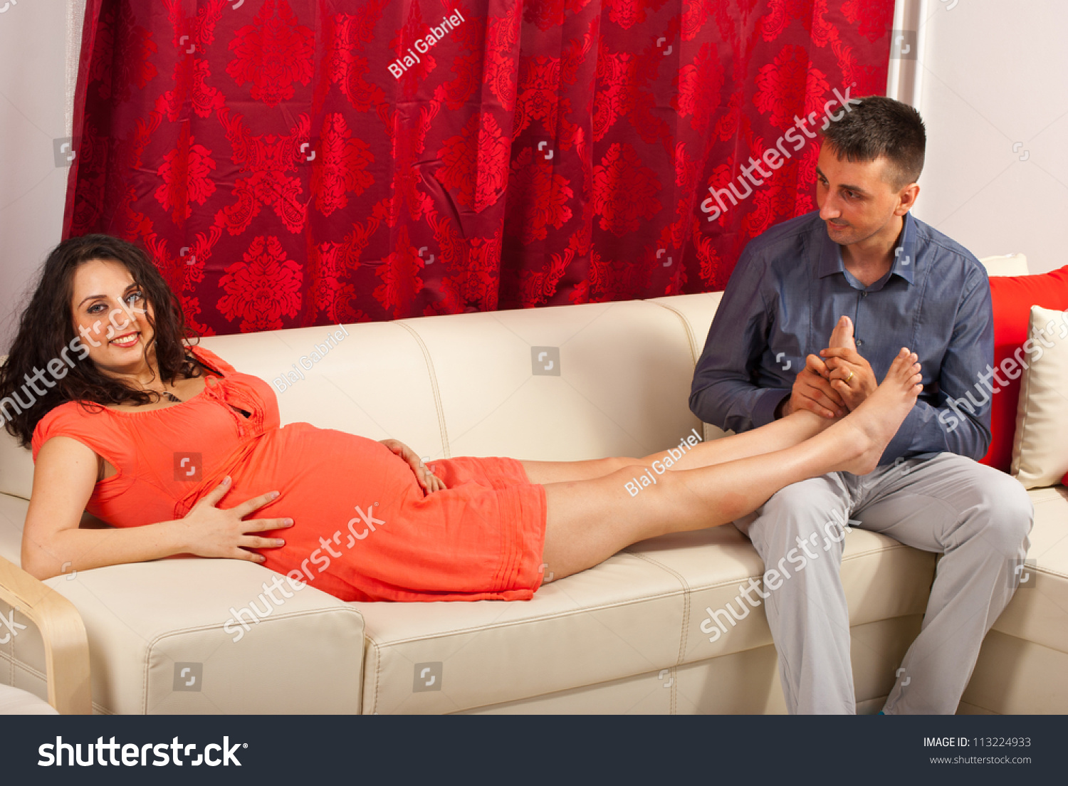 Husband massaging his pregnant wife legs and sitting together on couch in  their home
