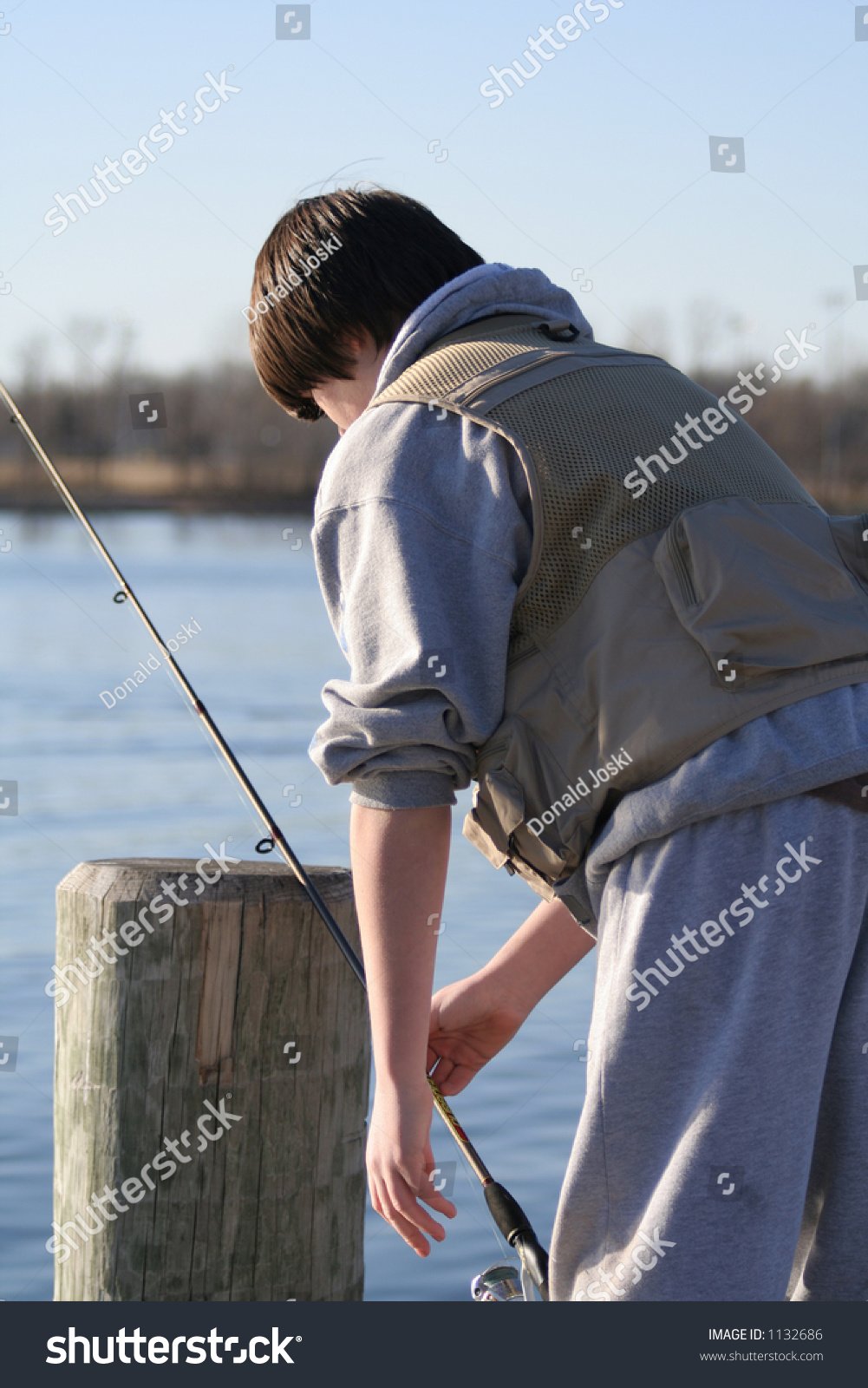 Teen fishing off of pier stock photo 1132686 shutterstock for Fishing off a pier