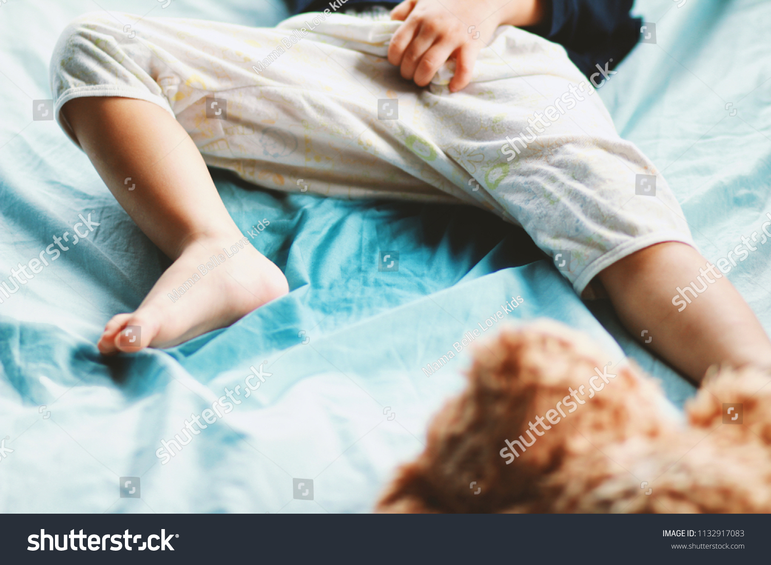 Image of Bed-wetting situation in toddler baby boy.Boy wet the bed and touch  his penis while he was sleeping.Selective focus.Stop using diaper or Potty  ...