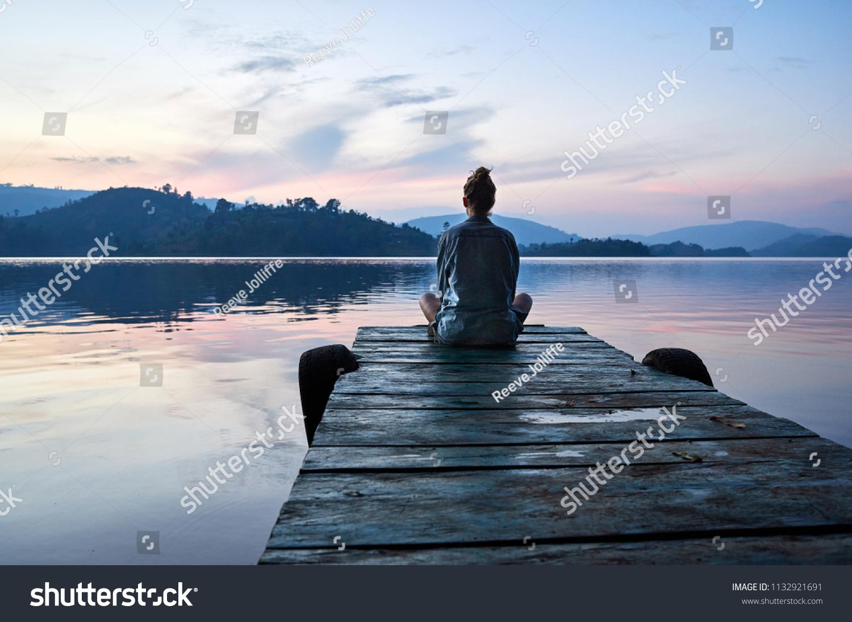Peaceful lifestyle shot of woman sitting on dock at sunset on Lake Bunyonyi, Uganda, Africa. #1132921691