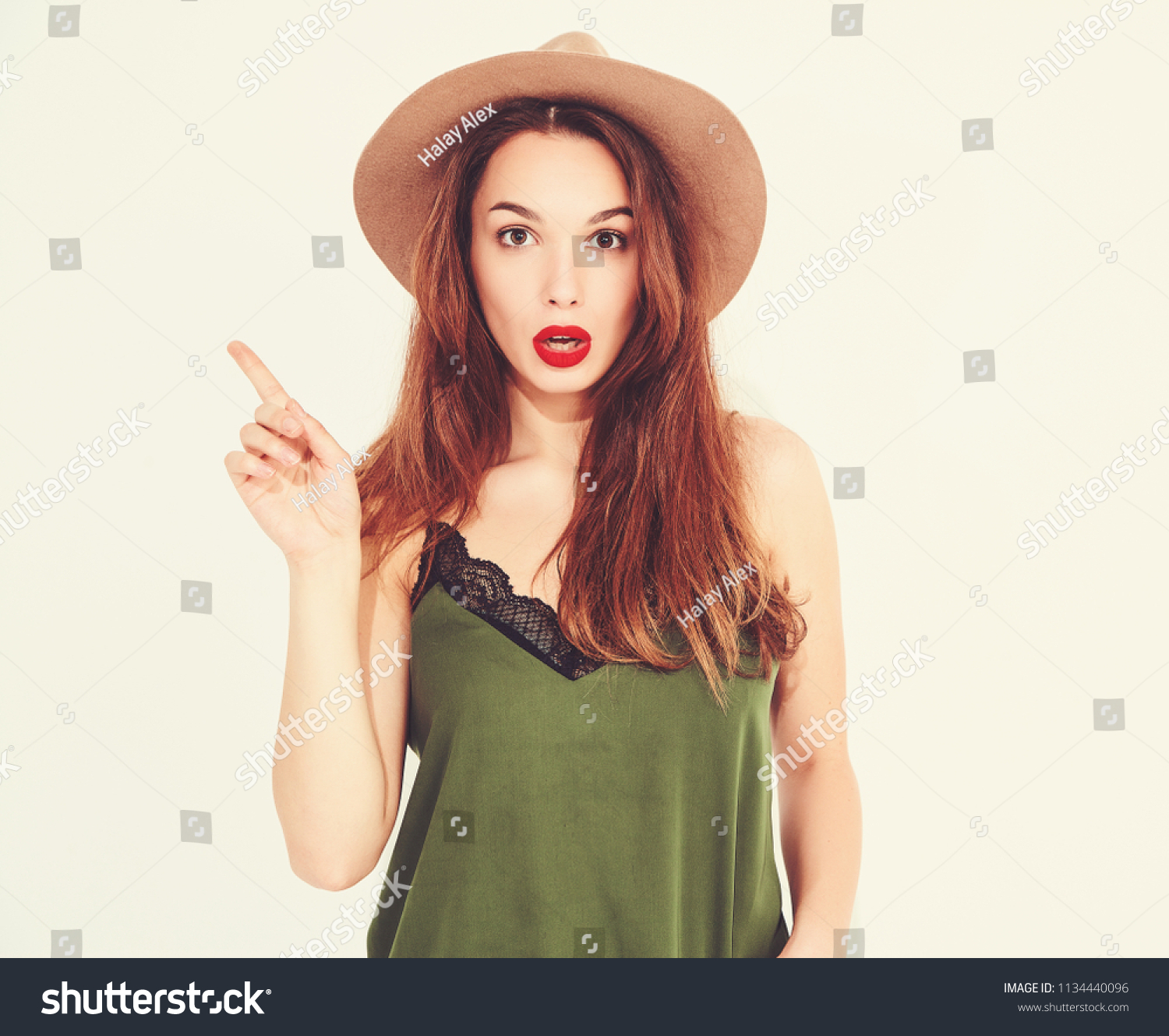 502383ca67b75 Young stylish girl model in casual summer green clothes and brown hat with  red lips got