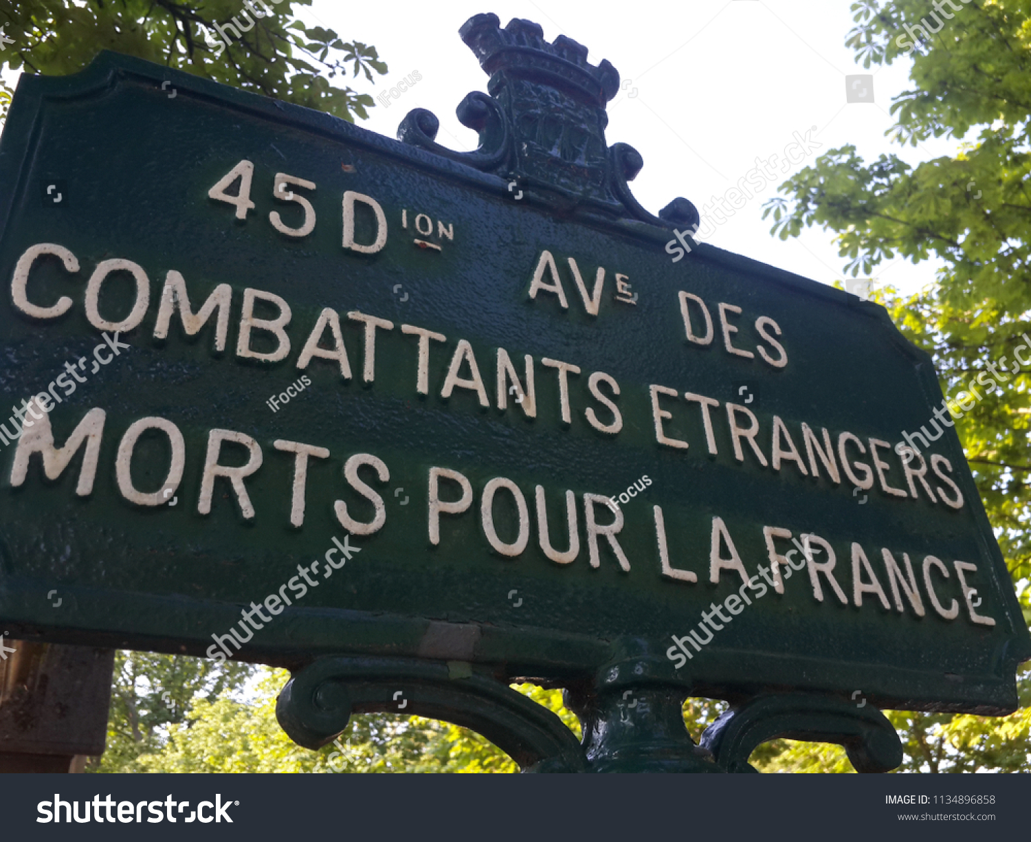PARIS, FRANCE - JUNE 30, 2018: A street name plate commemorates foreign fighters on the grounds of Pere Lachaise cemetery, on June 30, 2018 in Paris, France.