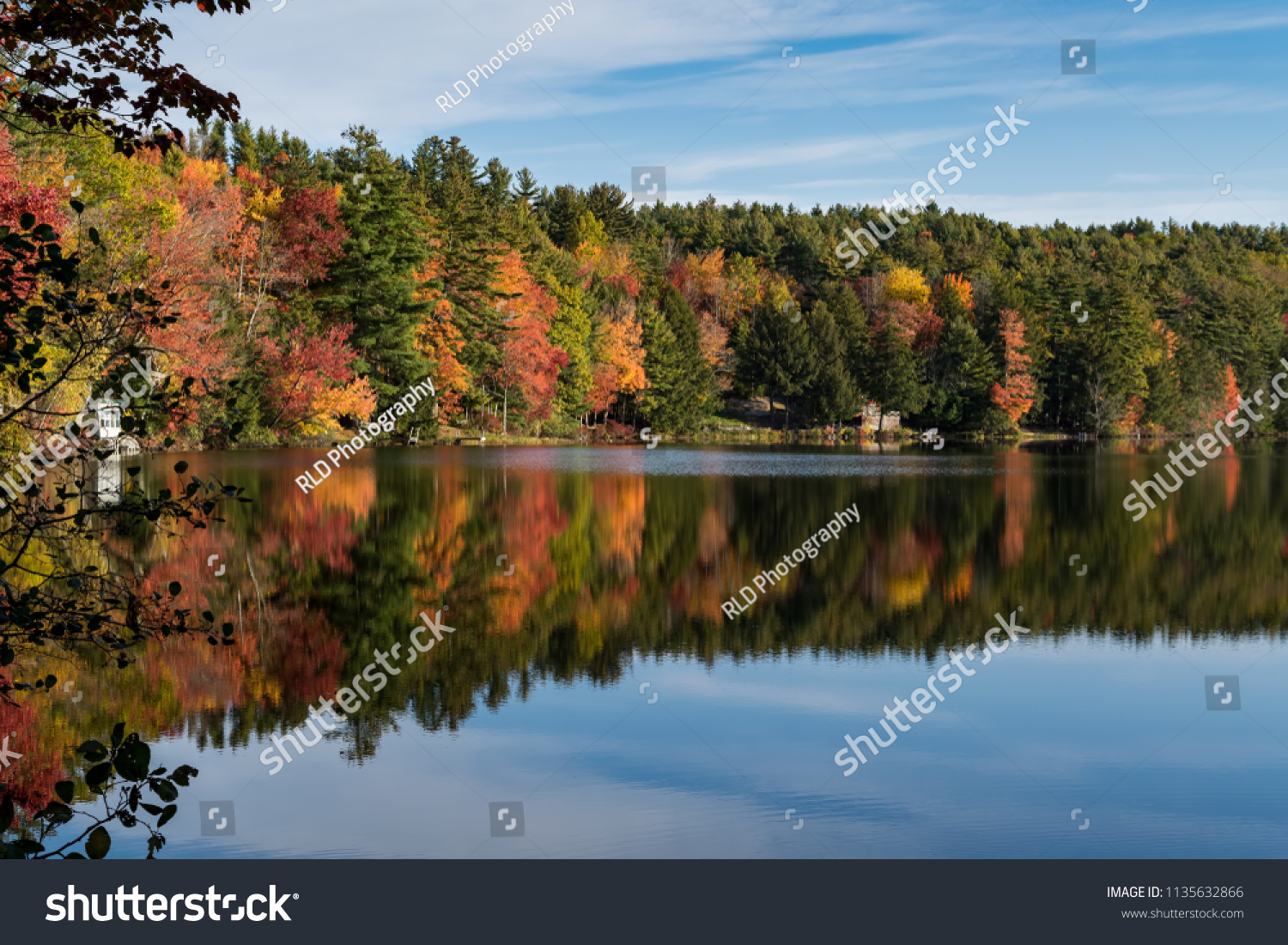 An image of a country pond in autumn with bright forest colors reflected in the water