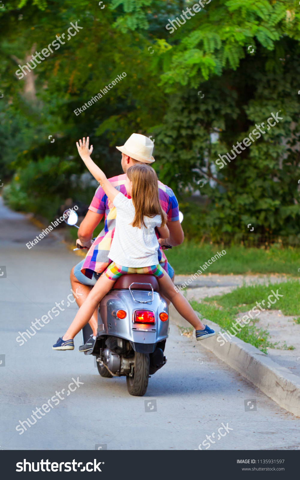 Father and daughter riding a vintage scooter in the street wearing hats.  Holiday and travel 73468d778e1