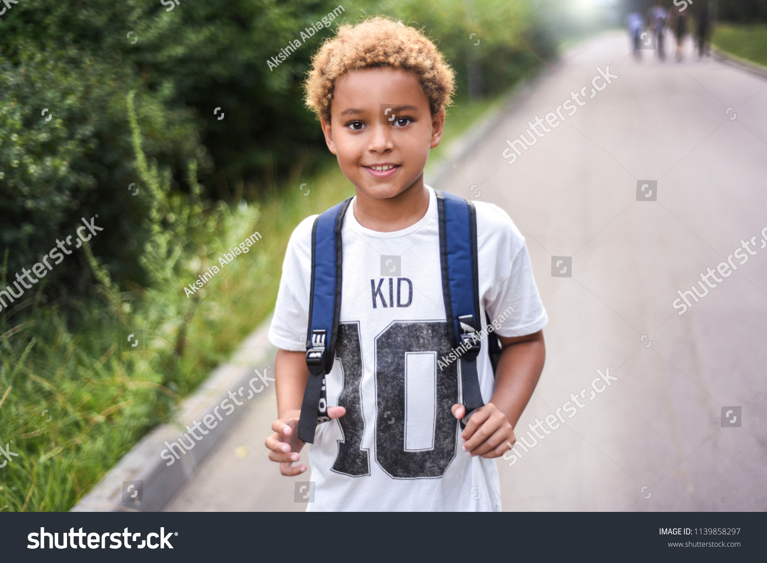 Portrait of the cute african american boy who is going to school with his school  backpack. Student mixed boy on his way to the school. Study for children. Road. Shooting on the july 2018.  #1139858297