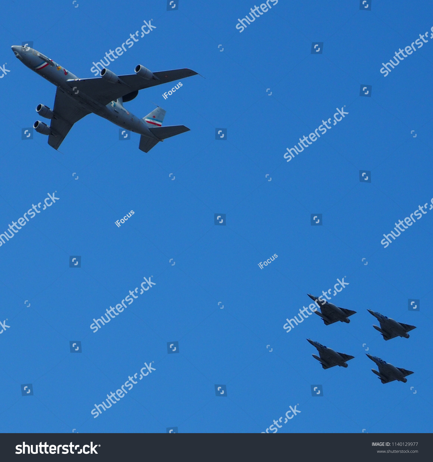 PARIS, FRANCE - JULY 14, 2018: A Boeing AWACS 1E3F and Mirage 2000 jet fighters fly over the French capital on July 14, 2018 in Paris, France.