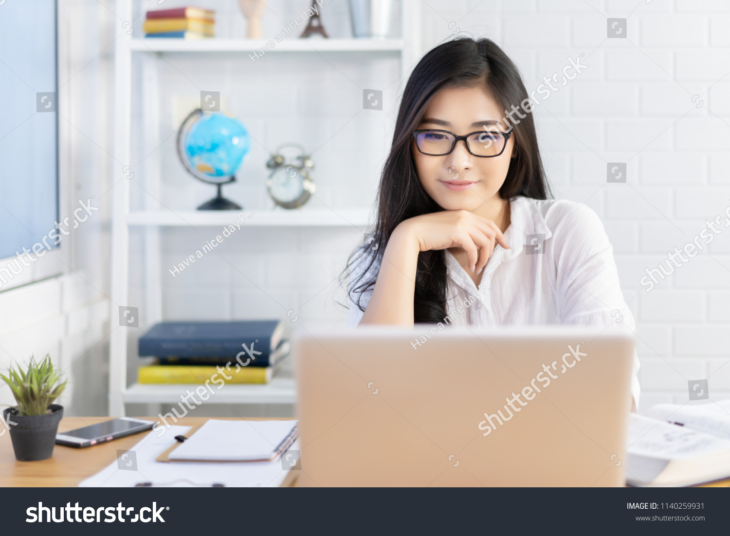 Education study abroad,Asian student girl with glasses look at laptop while doing homework making video call abroad using internet friend connection, business women use computer analysis finance data  #1140259931