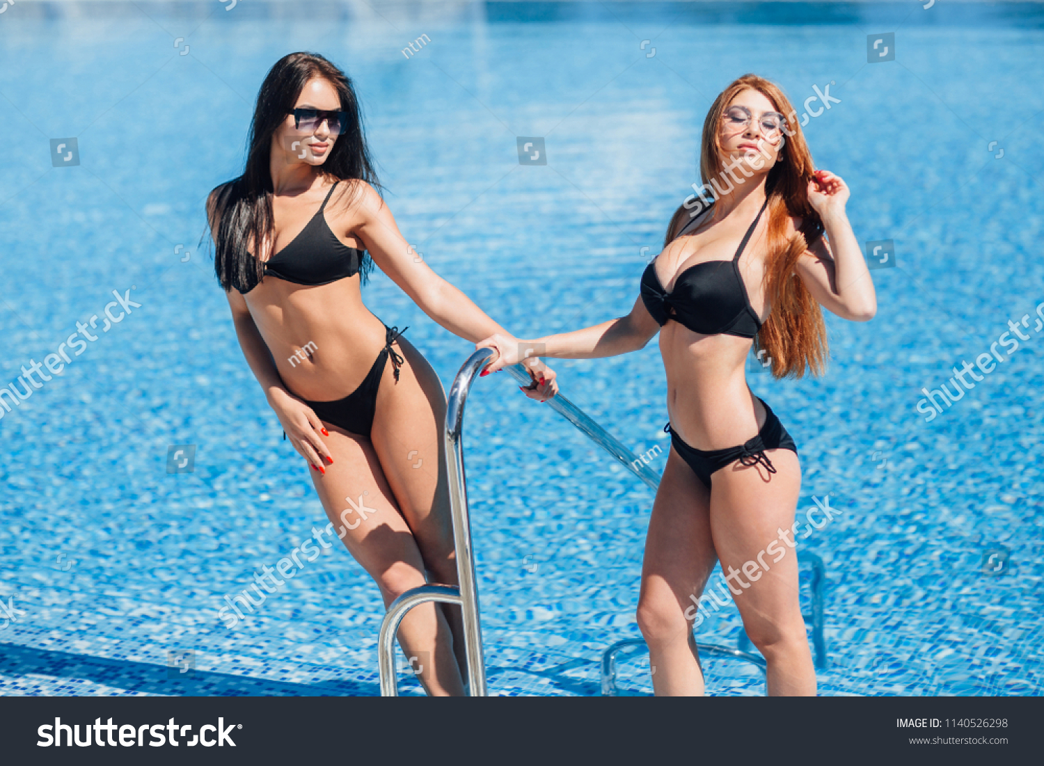 Two hot girls in black swimsuits and sunglasses posing and sunbathing at  the pool. Brunette