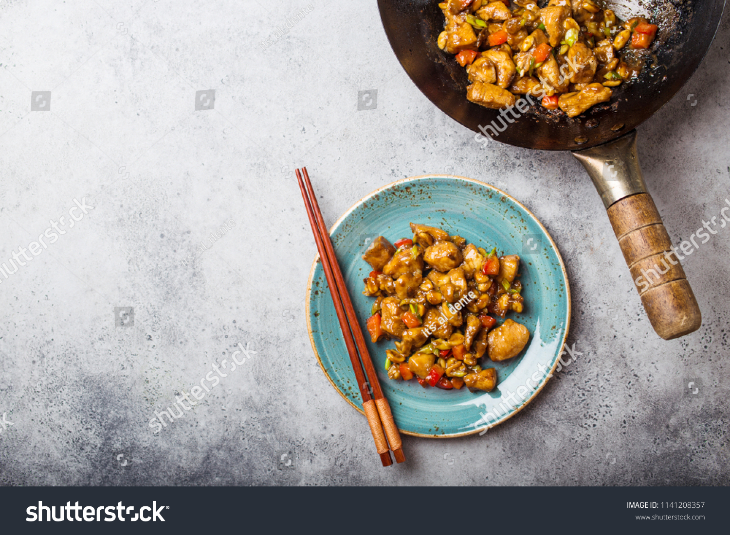 Top view of Kung Pao chicken on plate ready for eat, space for text. Stir-fried Chinese traditional dish with chicken, peanuts, vegetables, chili peppers. Chinese dinner, chopsticks, stone background  #1141208357