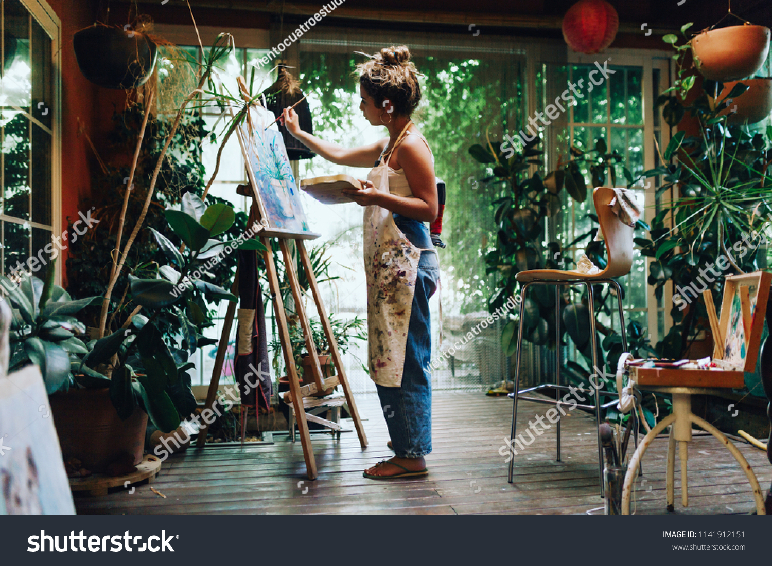 Indoor shot of professional female artist painting on canvas in studio with plants. #1141912151