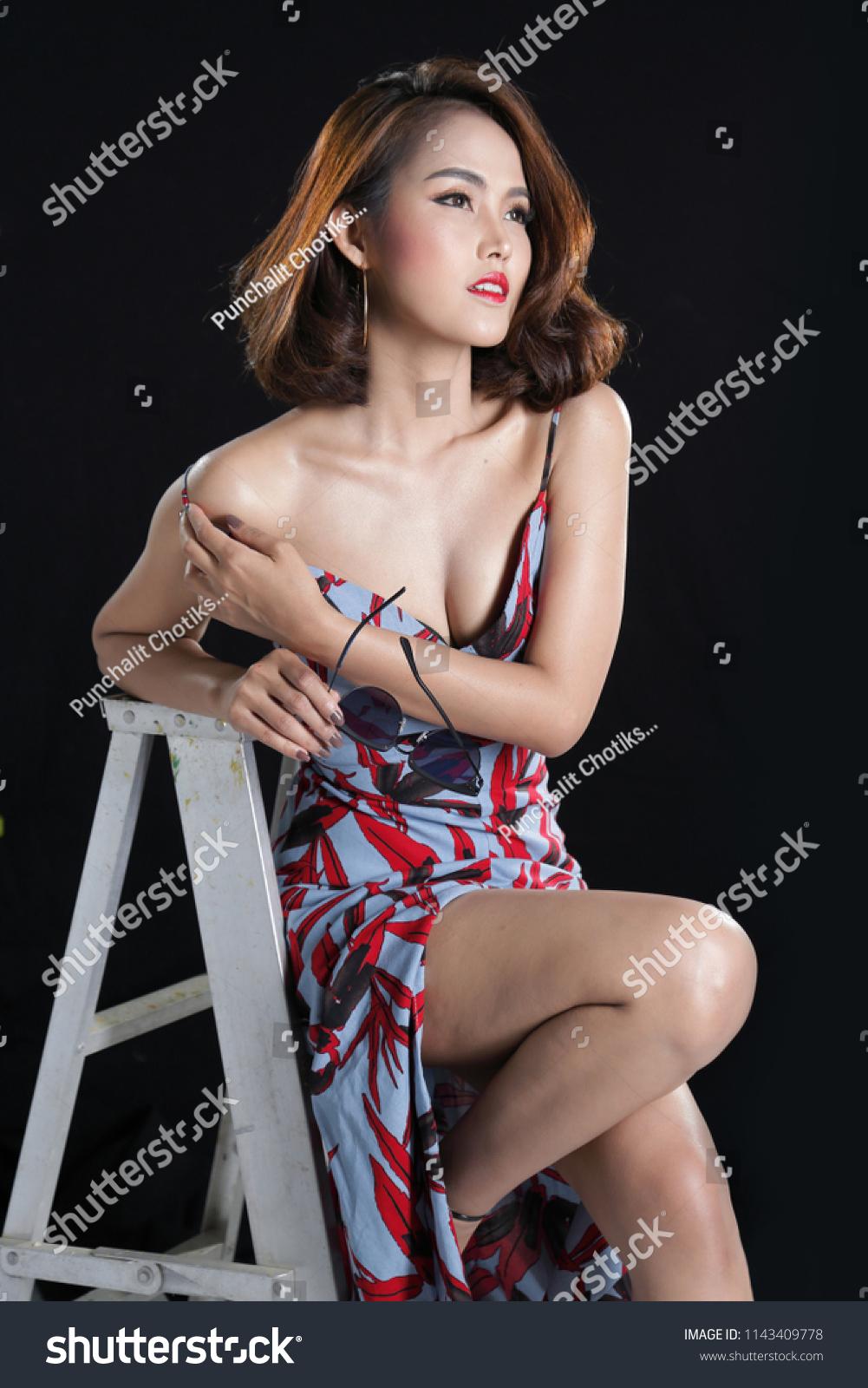 Sexy South East Asian woman posing in leaf print slinky split front  periwinkle blue dress in