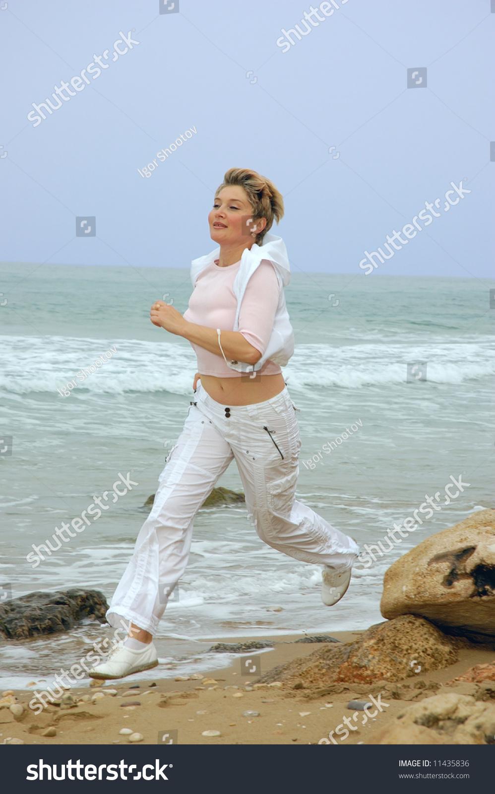 beautiful mature women running on beach stock photo (royalty free