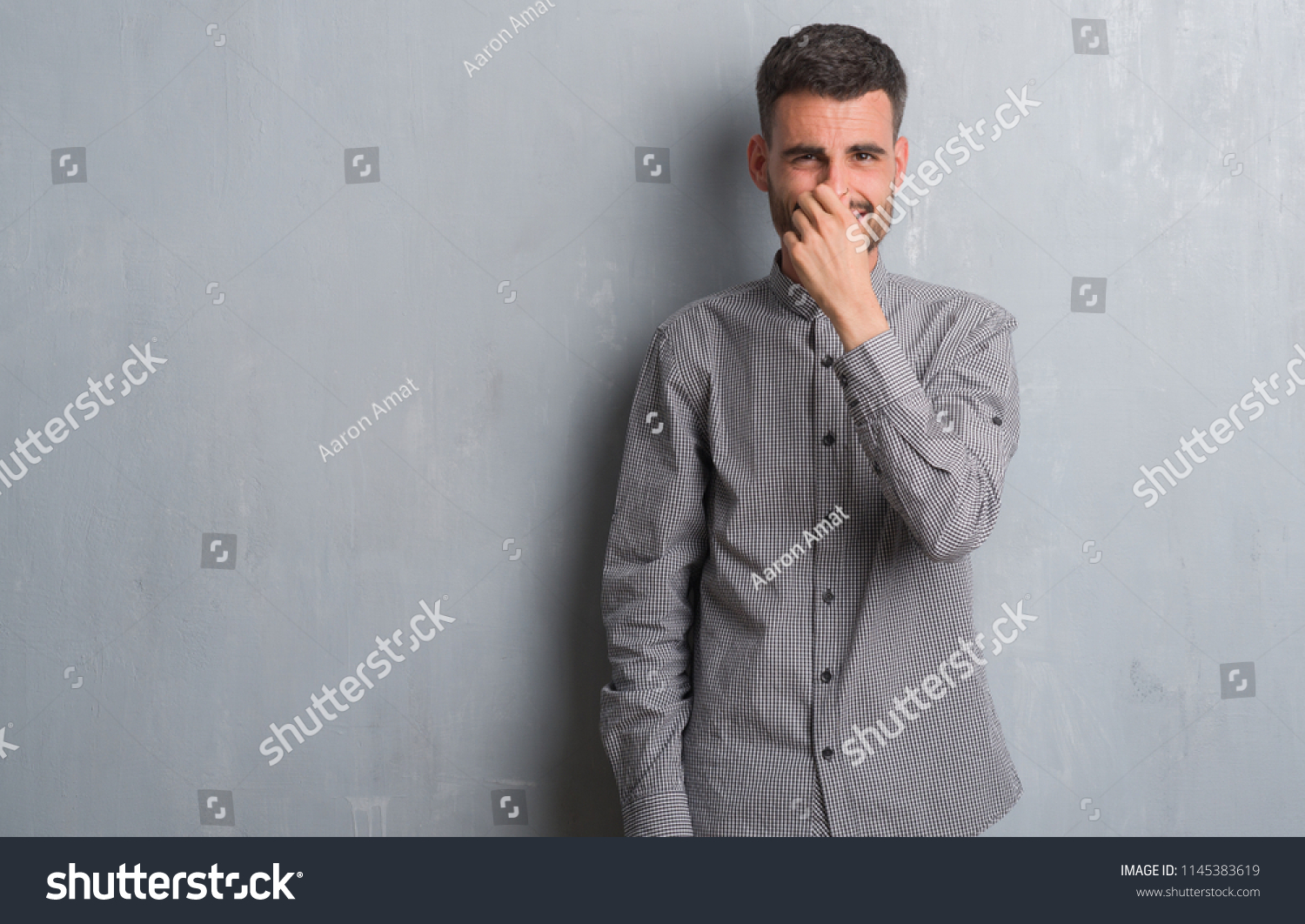 Young adult man standing over grey grunge wall smelling something stinky  and disgusting, intolerable smell