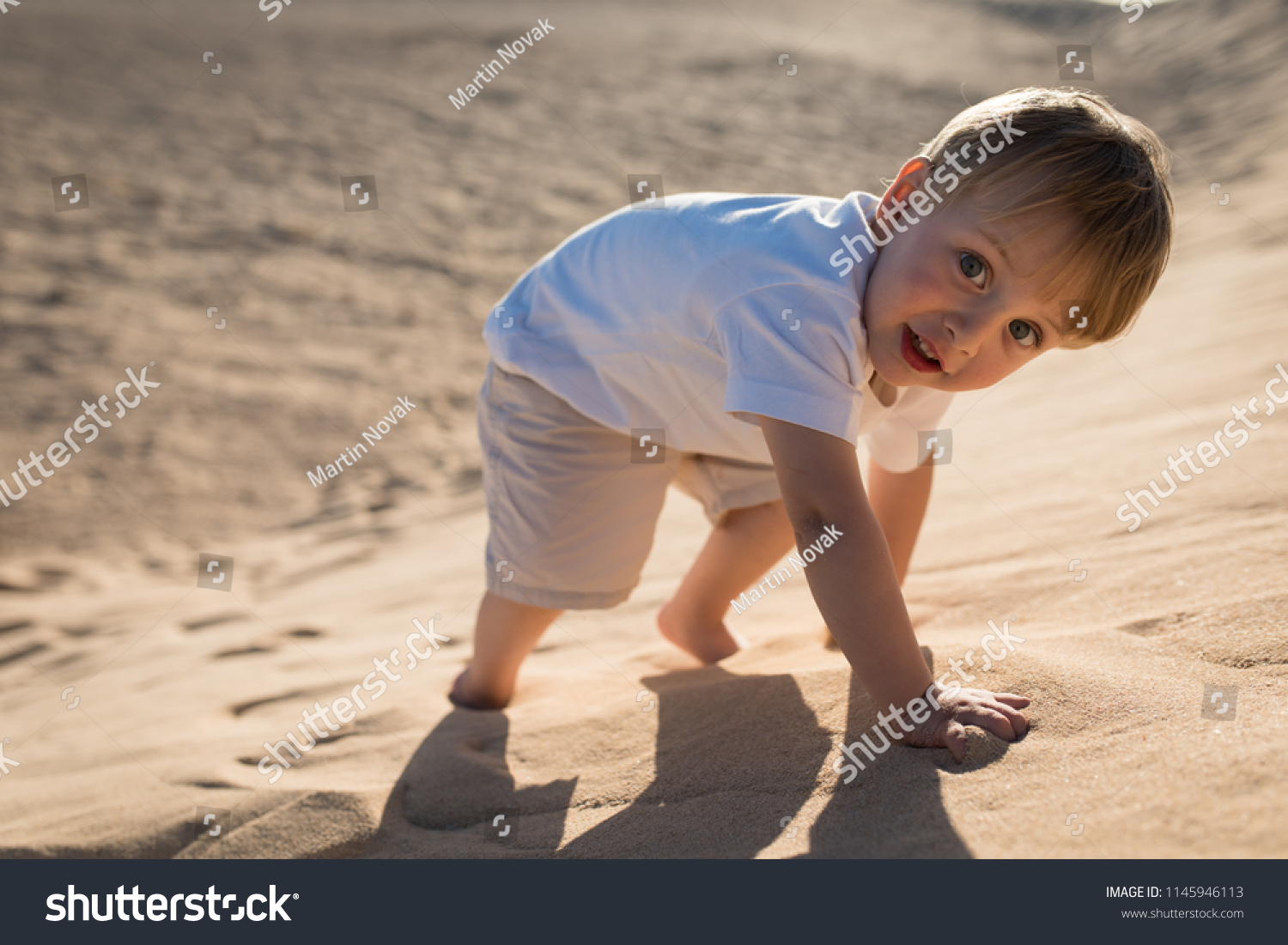 Little handsome courageous baby boy climbing on a sand dune.