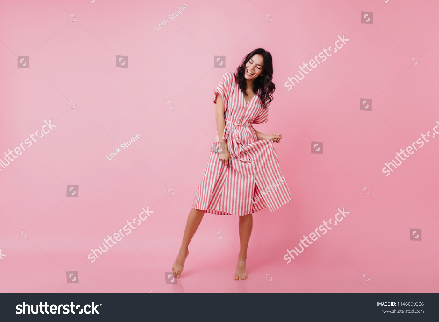 Shapely barefooted lady with tanned skin dancing on pink background. Happy caucasian girl in striped dress fooling around and laughing. #1146059306
