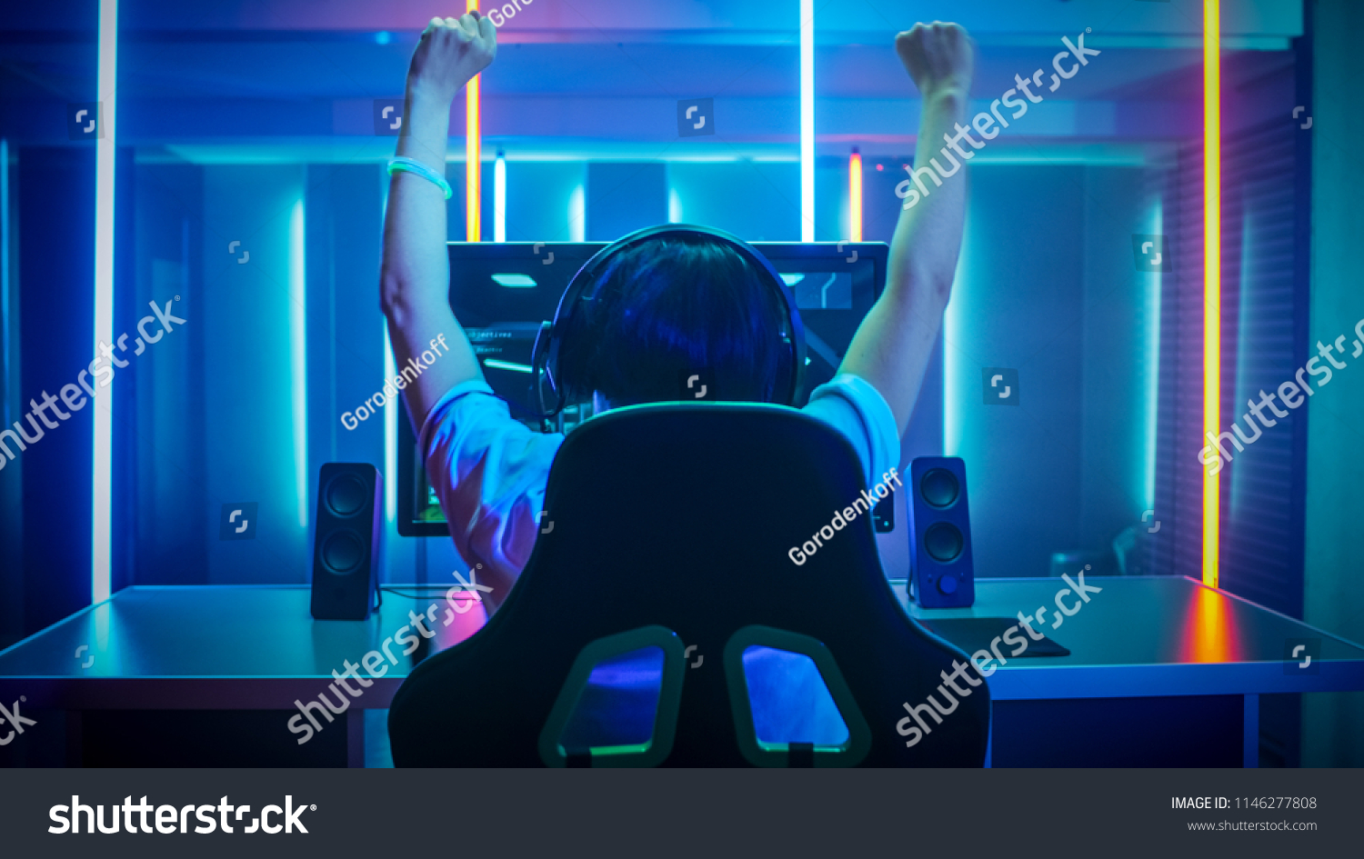 Professional Gamer Playing and Winning in First-Person Shooter Online Video Game on His Personal Computer. Footage Fade out into Bokeh. Room Lit by Neon Lights in Retro Arcade Style.Cyber Championship #1146277808
