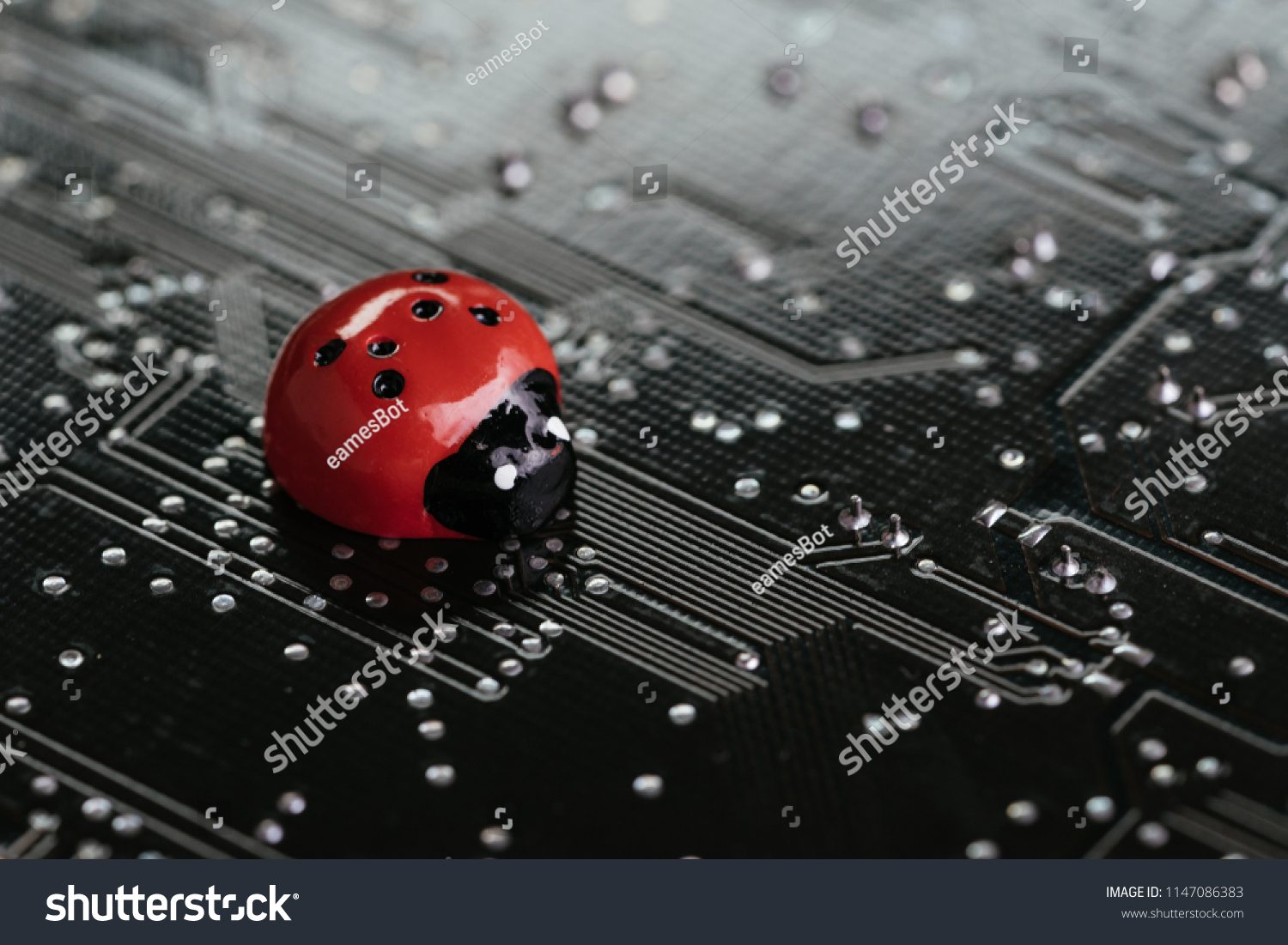 Computer bug, failure or error of software and hardware concept, miniature red ladybug on black computer motherboard PCB with soldering, programmer can debug to search for cause of error. #1147086383