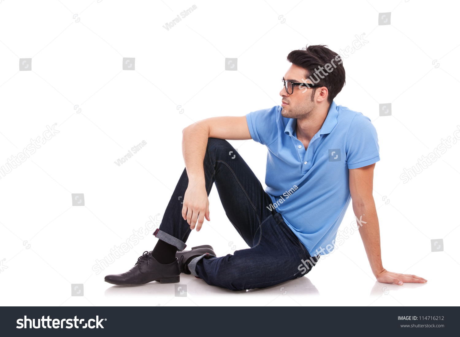 casual young man sitting on the floor and looking to a side away from the camera on a white. Black Bedroom Furniture Sets. Home Design Ideas